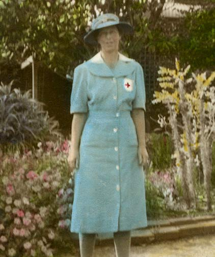 A vintage photograph of Miss Llewella Davies standing in vintage costume (with a hat) in a garden setting.