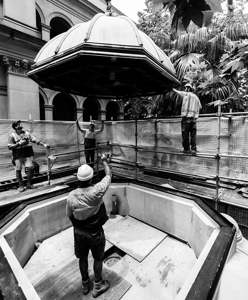 Workers lower the copper dome of the Sydney Hospital kiosk back on to the structure.