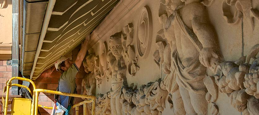 A stone worker restoring intrictate sandstone carving under the eaves at the Thomas Walker Hospital.