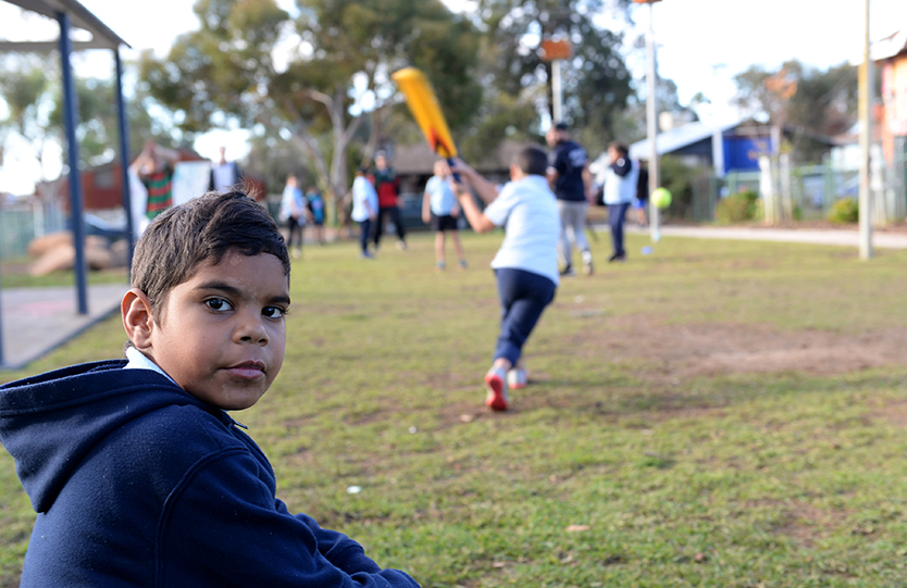 Children watching and playing cricket