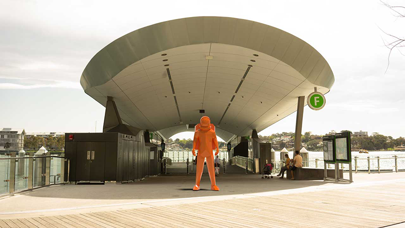 Orange astronaut sculpture standing in front of the Barangaroo ferry terminal in Sydney