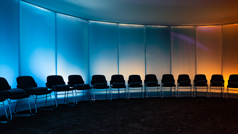 Row of chairs against curved wall lit in blue and yellow light