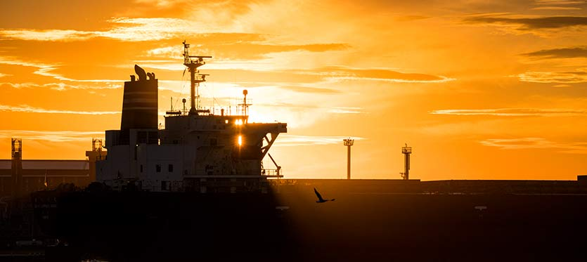 Silhouette of a cargo ship against the sunset.