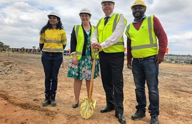 Minister Roberts with three other people, all wearing high-vis vests standing on an empty lot, with the Minister holding a shovel.