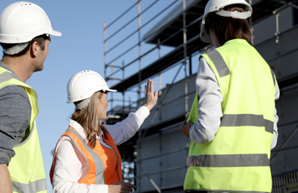 A female building certifier points scaffolding out to her colleagues on a building site.