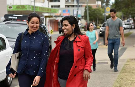 Two women walking along a sidewalk.