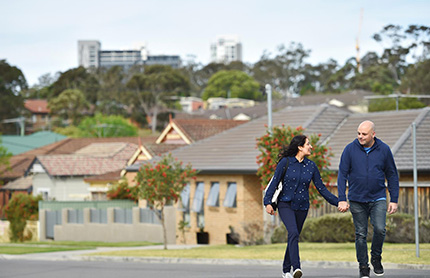 A couple, walking hand-in-hand along a suburban road.