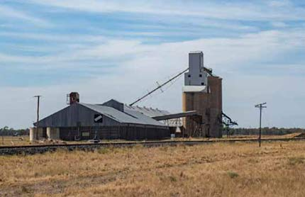 A grain silo and large shed, viewed from the other side of a railway track.