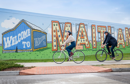 Couple riding their bicycles past the Welcome to Maitland Sign on Elgin St, Maitland