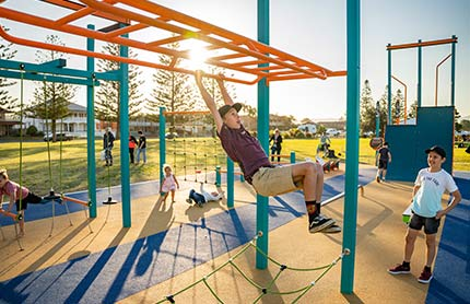 Late afternoon view of children playing on public playground equipment with a boy in the foreground swinging from monkey bars.