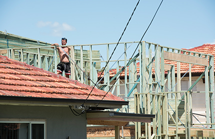 A builder works on a house under construction.