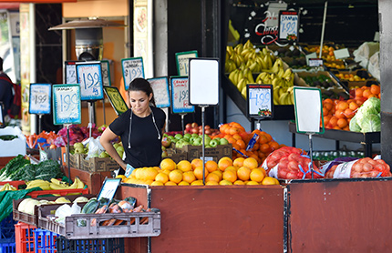 Woman picking fruit on Belmore Road shops in Riverwood, South Sydney NSW.