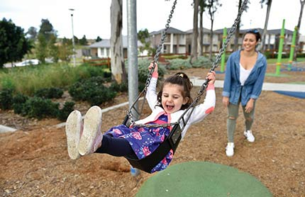 A mother pushing her child in a playground swing. The child is mid swing and laughing.