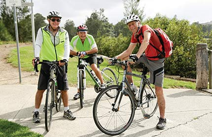 Three cyclists in an outdoor park, stopped on the path and smiling at the photographer.