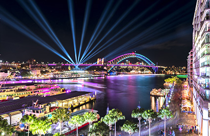Circular Quay and Sydney Harbour Bridge illuminated with colorful light, during the Vivid Sydney. Photo by RugliG / Shutterstock