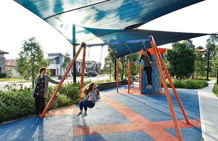 Two children swinging highly in a playground. An older female relative looks on.