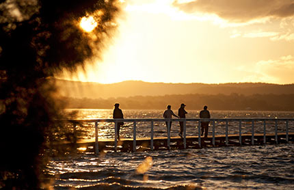 Tuggerah lake jetty with people standing on it at sunset