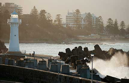 Lighthouse with waves crashing against rocks and apartments in the distance at Wollongong Harbour